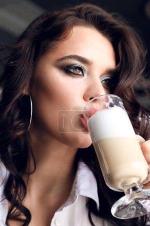 Photo pour Photo de mode de la belle jeune femme avec des cheveux bouclés sombre en élégante robe assis dans l'élégant restaurant - image libre de droit
