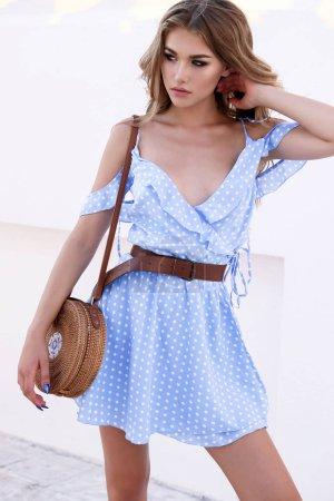 Photo pour Photo de mode en plein air de belle jeune femme aux cheveux blonds dans une élégante robe d'été et sac de paille de marche dans la ville - image libre de droit