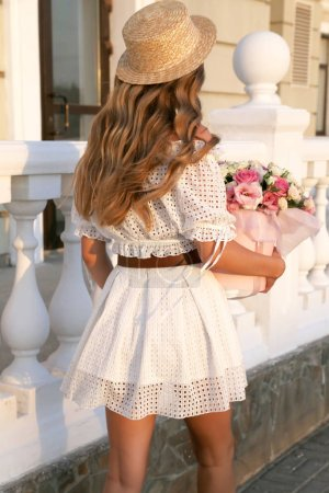 Photo pour Photo de mode en plein air de belle fille sexy avec des cheveux blonds dans une robe élégante marchant dans la rue avec bouquet de fleurs - image libre de droit
