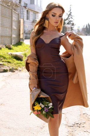 Photo for Fashion outdoor photo of beautiful woman with dark hair in elegant dress and coat walking by the street with bouquet of flowers - Royalty Free Image