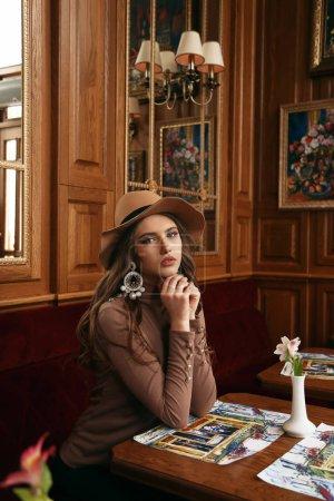 Photo pour Photo d'intérieur de mode de belle femme aux cheveux foncés dans des vêtements élégants et le har assis dans le café - image libre de droit