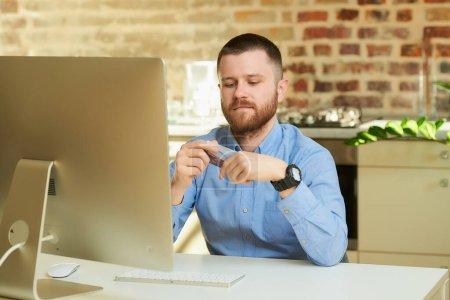 Photo pour Un homme à la barbe tient une carte de crédit et se prépare à faire des achats en ligne à la maison. Un mec qui fait un paiement en ligne sur Internet sur un ordinateur de bureau dans son appartement. - image libre de droit