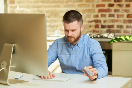 Photo pour Un homme pensif avec une barbe tape une information de carte de crédit pour faire des achats en ligne à la maison. Un mec qui fait un paiement en ligne sur Internet sur un ordinateur de bureau dans son appartement. - image libre de droit