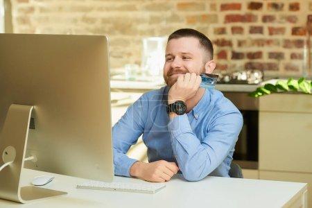 Photo pour Un homme heureux avec une barbe attend devant l'ordinateur et tient une carte de crédit à la maison. Un gars qui fait un paiement en ligne sur Internet sur un ordinateur de bureau dans son appartement . - image libre de droit