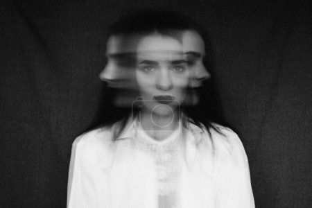 Photo for Crazy portrait of a girl with mental disorders and split personality. Black and white in vintage style with added grain and motion blur - Royalty Free Image