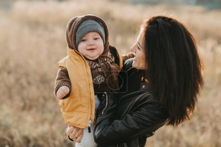 Photo for Joyful happy young mother with her baby boy boy son in her hands in the autumn field. Happy family has joy and fun - Royalty Free Image