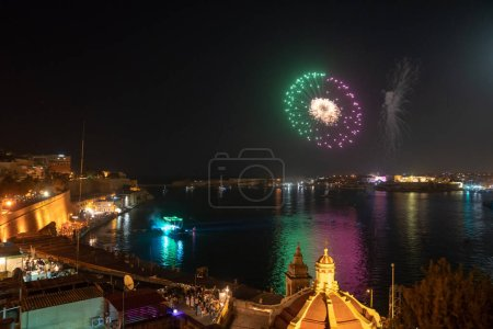 May 01, 2018. Valletta, Malta. Beautiful old town of Valletta at night with many people crowded by the coastline watching live show and waiting for the fireworks.