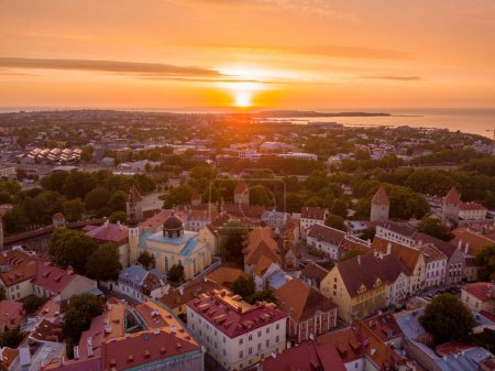 Beautiful orange sunset over old town of Tallinn in Estonia with the Raekoja plats, castle and old medieval towers.