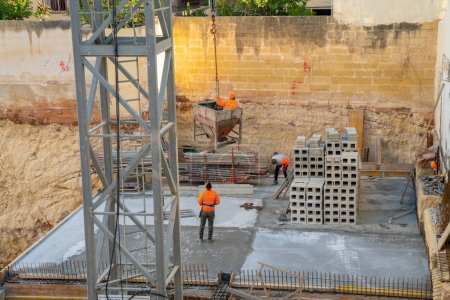 May 10, 2018. Valletta, Malta. Group of workmen wearing protective helmets and vests building a house using cranes bricks and concrete.