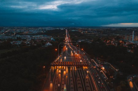Aerial night view of the traffic road with cars passing through the point of toll highway, toll station. Amazing landscape of highway interchange in Portugal, Europe.