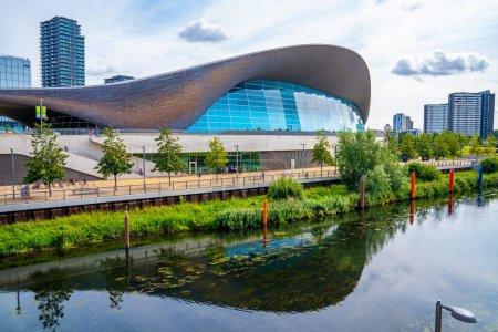 Foto de Foto del Parque Olímpico Reina Isabel, con el Centro Acuático de Londres y gente cruzando el puente en el fondo. - Imagen libre de derechos