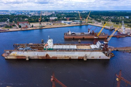 Photo for Riga, Latvia. July 20, 2020. Aerial view of the military ship being repaired in dry docks. Beautiful aerial industrial view of the ship. - Royalty Free Image