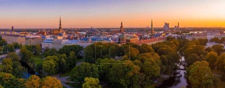 Photo pour Beautiful aerial panorama of Riga center and Vansu bridge over Daugava river during amazing sunset. View of illuminated Riga city, capital of Latvia. - image libre de droit
