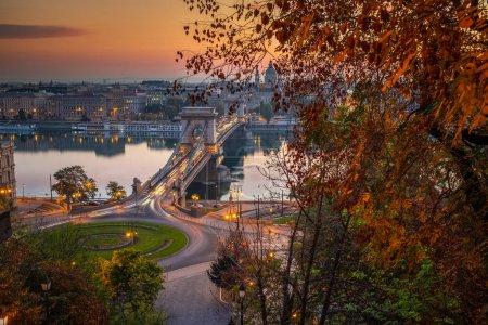 Photo pour Budapest, Hongrie - Le célèbre pont de la chaîne Szechenyi (Lanchid) et le rond-point Clark Adam Square au lever du soleil avec un beau feuillage d'automne - image libre de droit