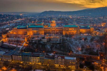 Photo for Budapest, Hungary - Aerial view of the snowy Buda Castle Royal Palace with beautiful golden sunset on a winter afternoon - Royalty Free Image