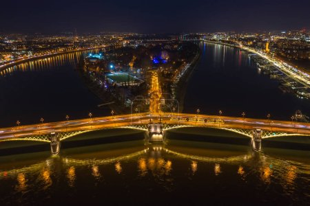 Photo for Budapest, Hungary - Aerial view of the illuminated Margaret Bridge with yellow tram on it and Margaret Island at background by night - Royalty Free Image