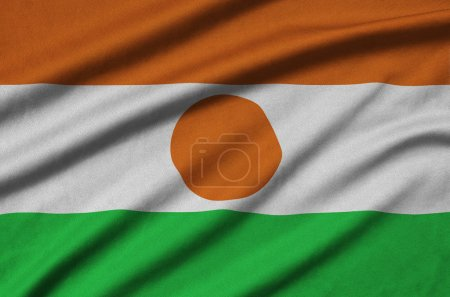 Niger flag  is depicted on a sports cloth fabric with many folds. Sport team waving banner