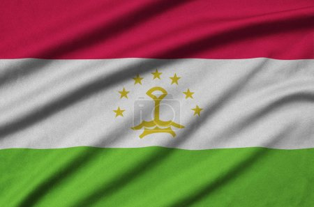 Tajikistan flag  is depicted on a sports cloth fabric with many folds. Sport team waving banner