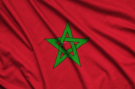 Morocco flag  is depicted on a sports cloth fabric with many folds. Sport team waving banner