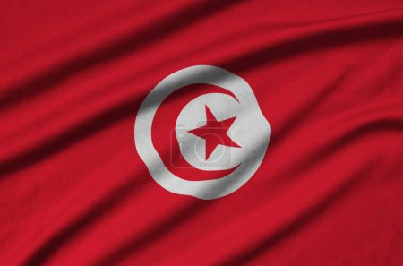 Tunisia flag  is depicted on a sports cloth fabric with many folds. Sport team waving banner