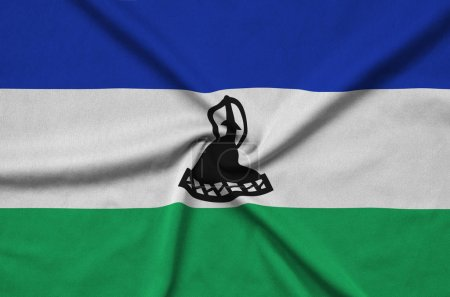 Lesotho flag  is depicted on a sports cloth fabric with many folds. Sport team waving banner