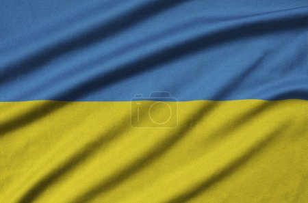 Ukraine flag  is depicted on a sports cloth fabric with many folds. Sport team waving banner