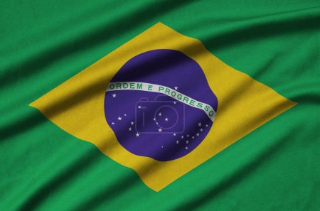 Brazil flag  is depicted on a sports cloth fabric with many folds. Sport team waving banner