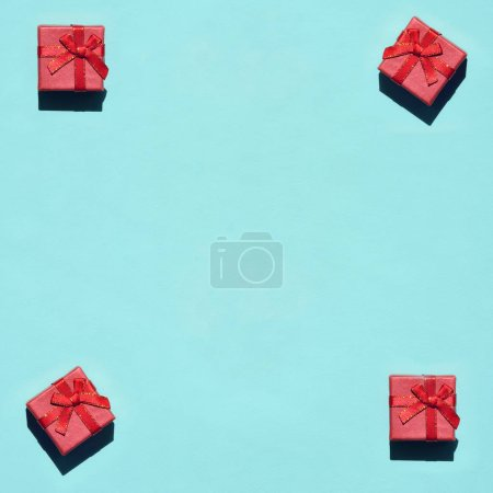 Many small red pink gift boxes on texture background of fashion trendy pastel blue color paper in minimal concept. Abstract pattern.
