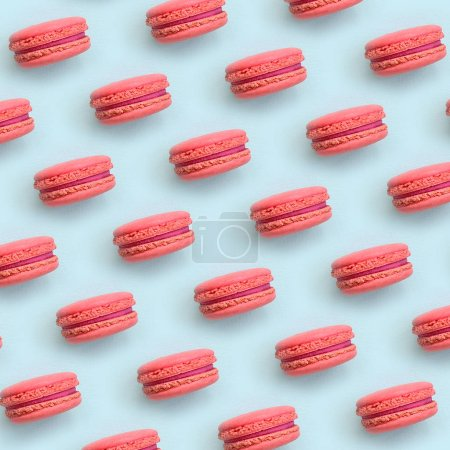 Pink dessert cake macaron or macaroon on trendy pastel blue background top view. Flat lay pattern composition.