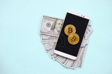 Bitcoins lies on a smartphone and hundred dollar bills on a light blue background.