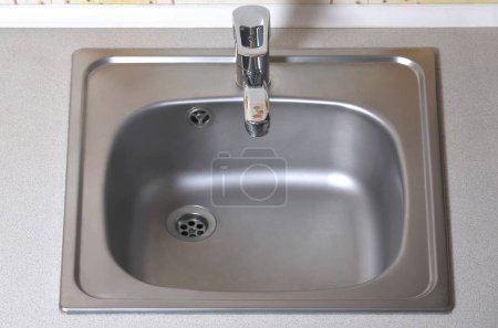 Sink with silver faucet. Built-In domestic kitchen appliances. New equipment installed in the kitchen counter