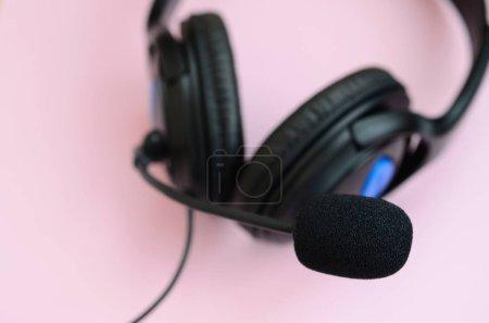 Photo pour Casque noir repose sur un fond rose pastel coloré. Concept d'écoute musicale - image libre de droit