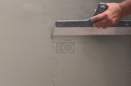 Photo for Hands of an old manual worker with wall plastering tools renovating house. Plasterer renovating outdoor walls and corners with spatula and plaster. Wall insulation. Construction finishing works - Royalty Free Image