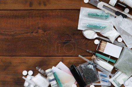 Beaucoup de substances narcotiques et de dispositifs pour la préparation de drogues reposent sur une vieille table en bois