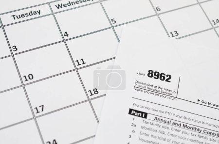 Photo pour IRS Formulaire 8962 Attestation d'impôt sur les primes CTP vide se trouve sur la page du calendrier vide. Concept de période fiscale. Espace de copie pour le texte - image libre de droit