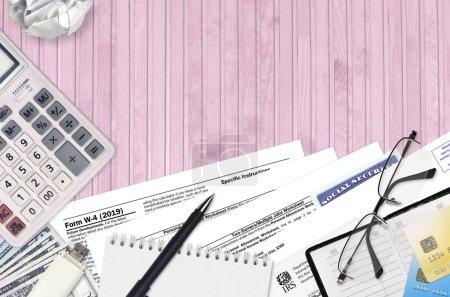 Photo pour Formulaire w-4 du SRI Le certificat de retenue des employés se trouve sur une table de bureau plate et prête à être remplie. U.S. Internal revenue services paperwork concept. Il est temps de payer des impôts aux États-Unis. Vue du dessus - image libre de droit