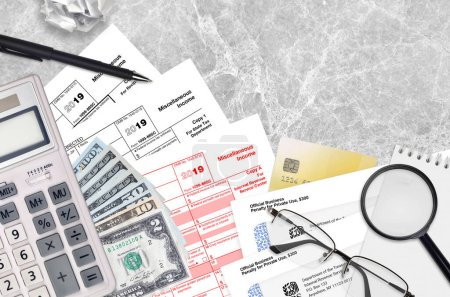 IRS form 1099-MISC Miscellaneous income lies on flat lay office table and ready to fill. U.S. Internal revenue services paperwork concept. Time to pay taxes in United States. Top view