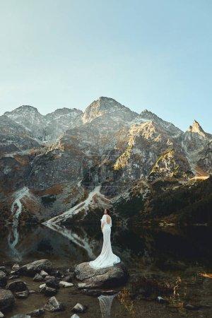 Photo pour Une belle mariée marche près d'un lac dans les montagnes - image libre de droit