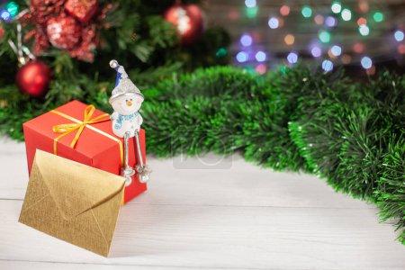 Photo pour Figure d'un bonhomme de neige assis sur un cadeau en papier rouge à côté d'une enveloppe d'or qui se trouve sur une table en bois blanche à côté d'une guirlande verte en arrière-plan une guirlande colorée de Noël - image libre de droit