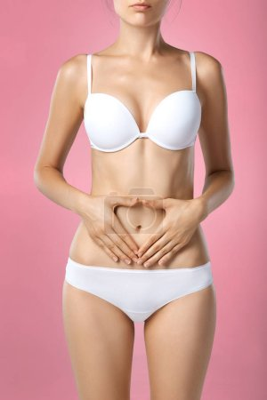 Photo for Woman health problem. Closeup of female with fit slim body in panties and bra suffering from pain and holding her hands on the stomach. Digestive disorders, period pain, health issues concept - Royalty Free Image