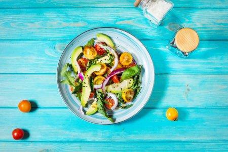 Photo pour Salade de tomates et d'avocat sur fond en bois bleu. Vue de dessus - image libre de droit