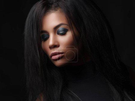 Photo pour Gros plan portrait à la mode d'une belle jeune femme mulâtre aux yeux serrés, aux lèvres pleines et aux cheveux noirs et amples. Tournage en studio d'une mannequin afro-américaine avec le maquillage lumineux sur son visage - image libre de droit