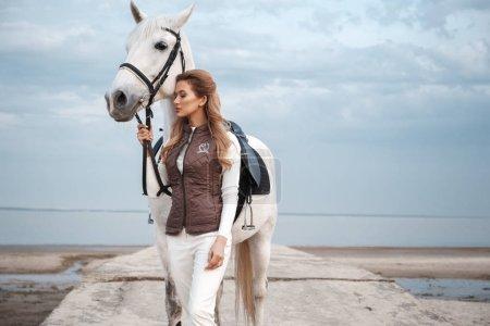 Photo pour Charmante et belle jeune femme portant une tenue de jockey élégant tient les rênes et pose avec le cheval blanc sur la côte près de l'eau. Un coureur attrayant pose à l'extérieur. Paysage naturel - image libre de droit