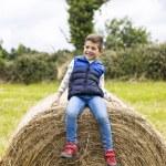 Cute boy on top of a straw bale...