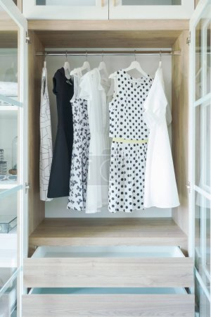 Photo for Dresses hanging on rail in wooden closet - Royalty Free Image