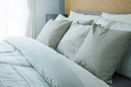 Photo for Closeup beige pillows on comfortable bed at home - Royalty Free Image