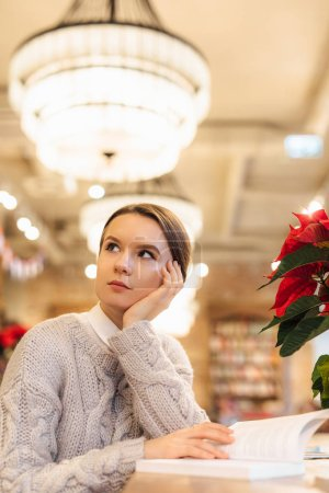 Photo for Clever girl sit at cafe and read a interesting book with boring face. Wear white sweater. Winter, autumn outfit. - Royalty Free Image