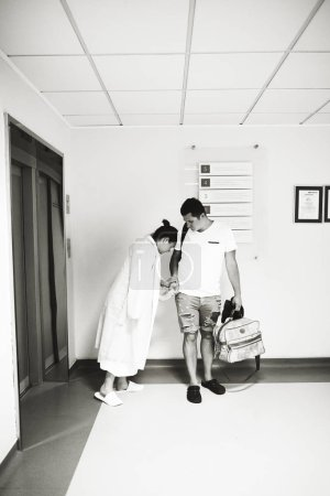Photo pour Un mari et sa femme attendent un ascenseur dans l'hospital.l maternelle. La femme a un scramble et ça lui fait mal - image libre de droit