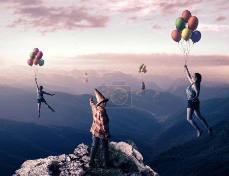 Photo pour Jeune homme au sommet d'une montagne pointent vers les gens qui volent avec des ballons au-dessus des montagnes.Le concept de rêve devient réalité . - image libre de droit