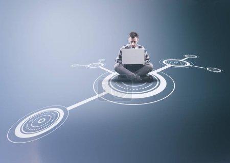 Photo pour Homme travaillant sur un ordinateur portable au milieu d'un réseau  . - image libre de droit